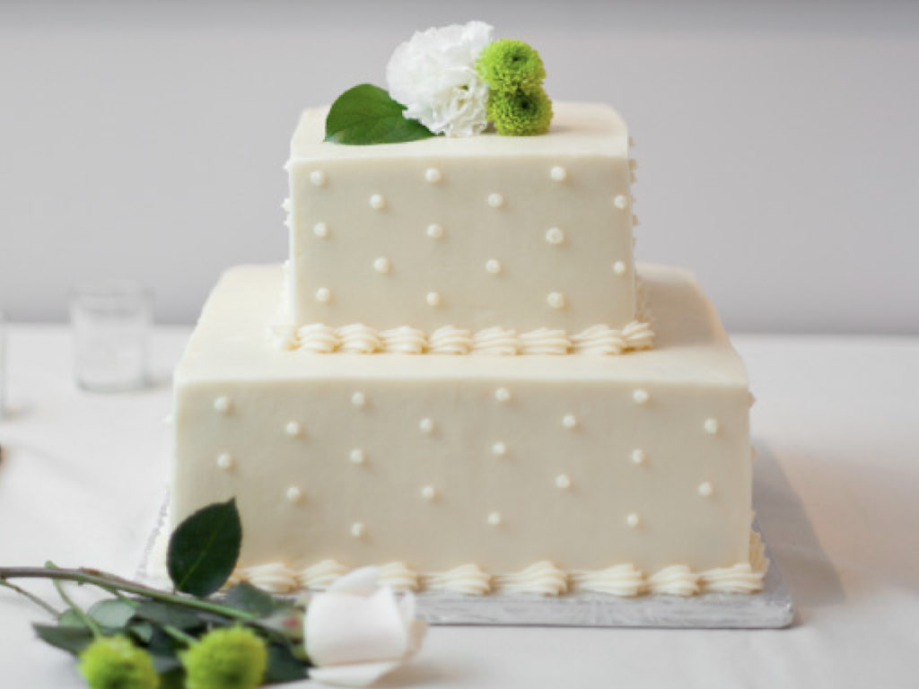 2 tier square cake with white frosring and polka dots on it