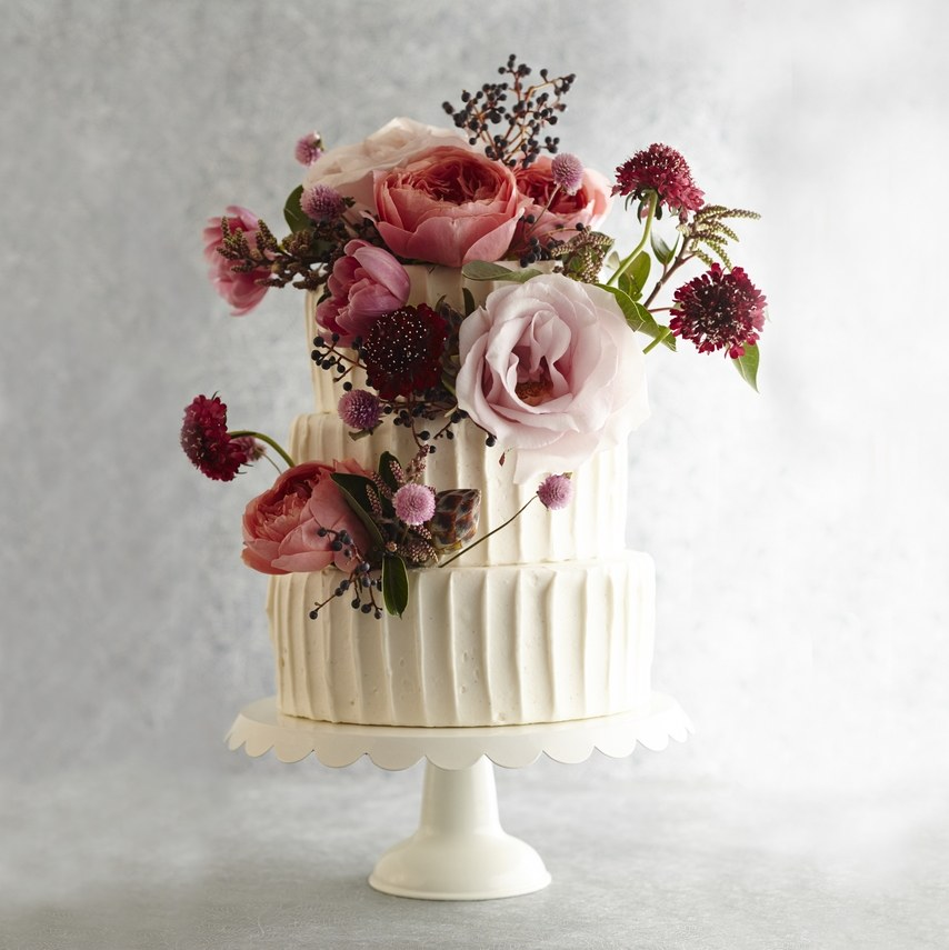3 tier white frosted cake with pink flowers on it