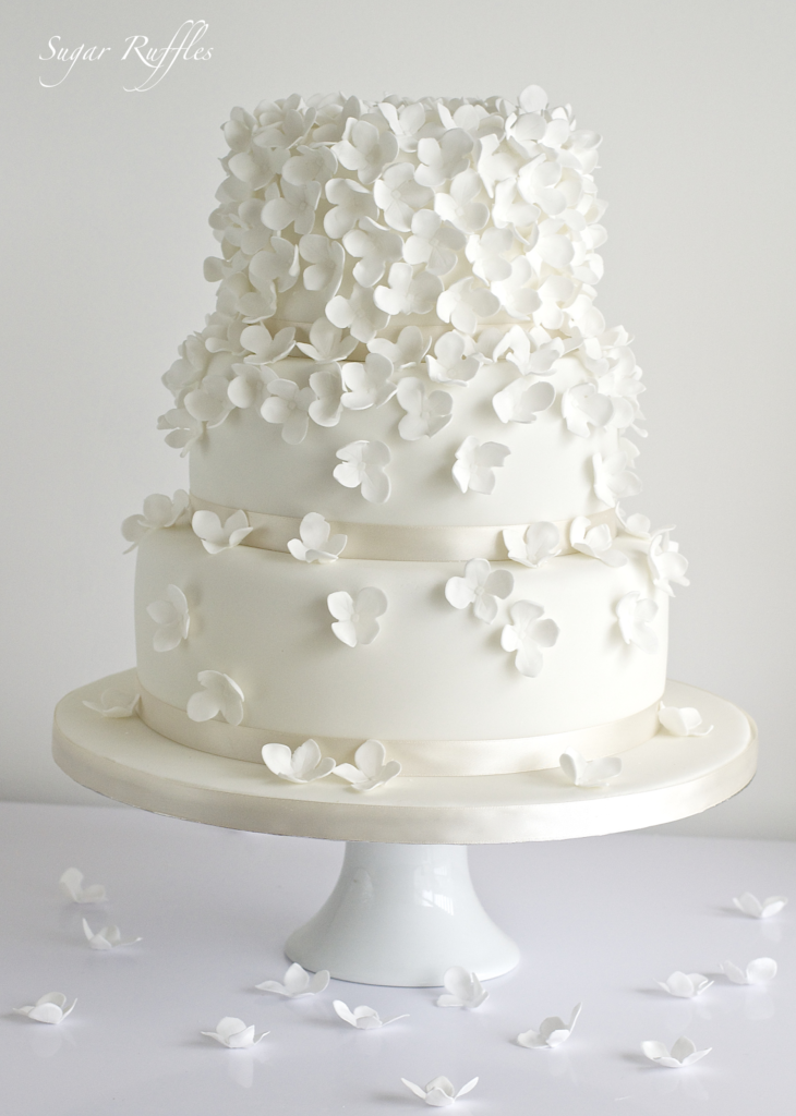 3 tier white cake with white hydrangea flowers