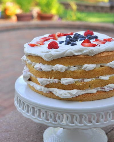 4 layer cake with white frosting and blueberries and strawberries on top