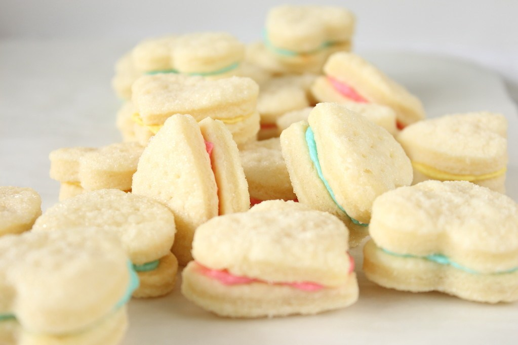 Many heart shaped wafer cookies filled with pink blue and yellow cream