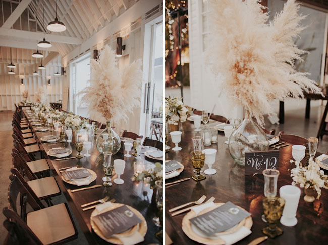long table with gold charger and big glass vases with beach grass in them