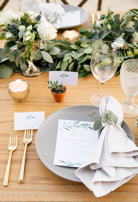 gray plate with gold silverware and greenery centerpiece