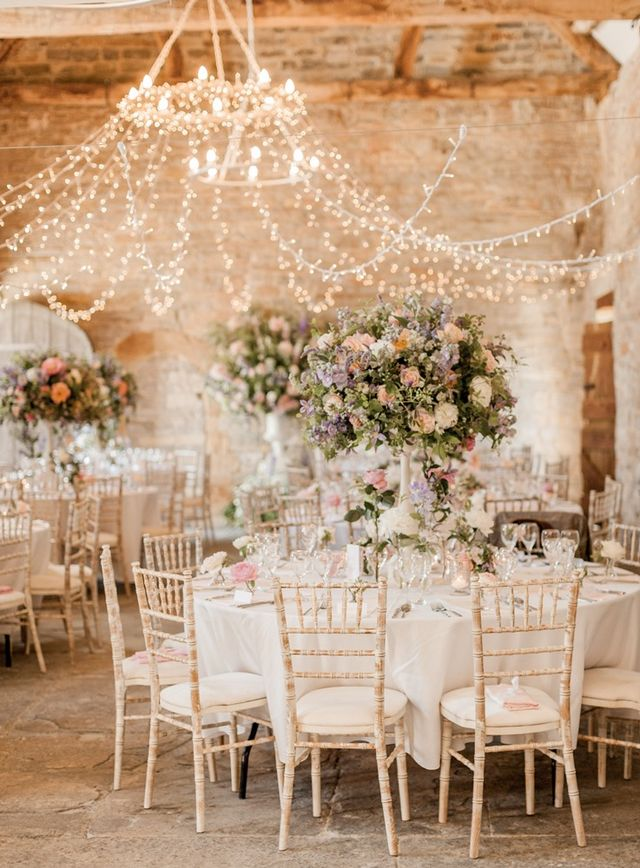 round table with white chippy chairs and tall centerpiece with purple and pink flowers