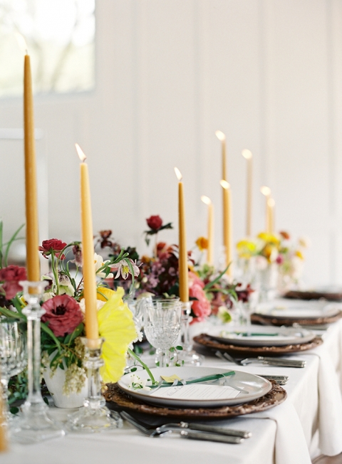 tall yellow candles with pink and green flowers in the centerpiece of white table with bronze chragers
