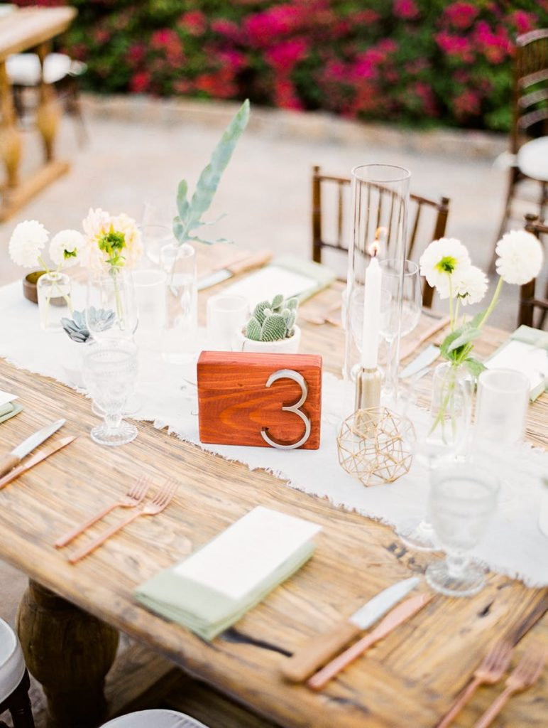 wood table with copper silverware and white table runner with clear glass vases and cups