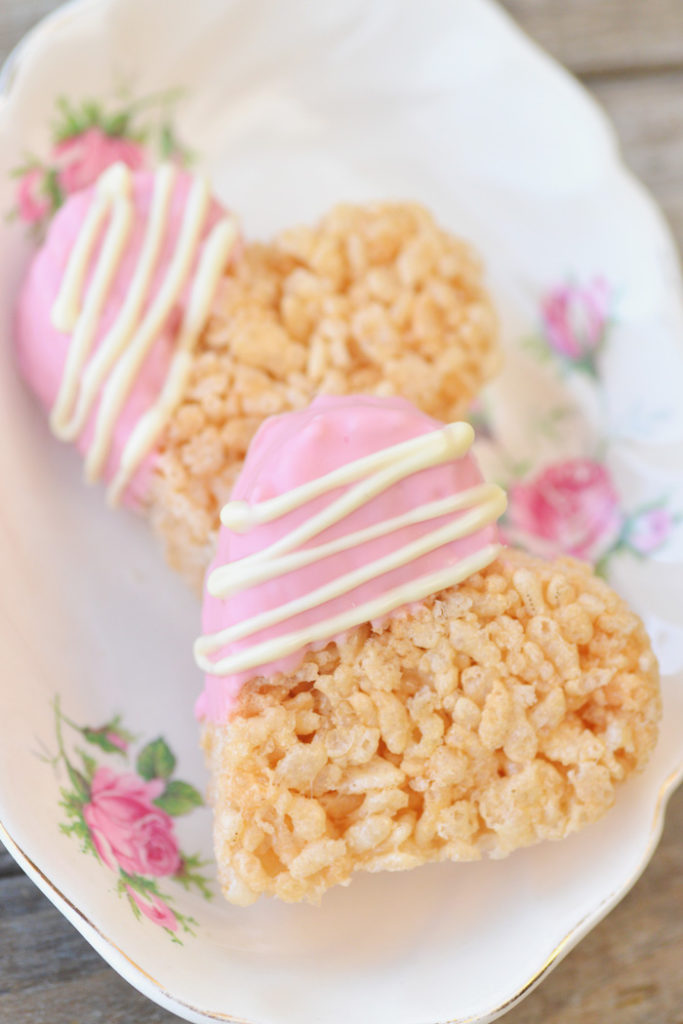 2 heart shaped rice krispies with corner dipped in pink with lines of white