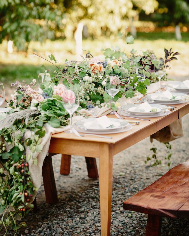 wood table with lots of greenery and pink and orange flowers running table white setting of 8 white plates