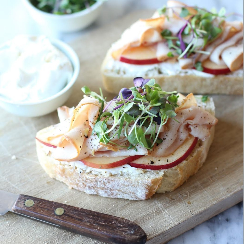 2 open faced sandwiches with apples turkey and sprouts on wood cutting board