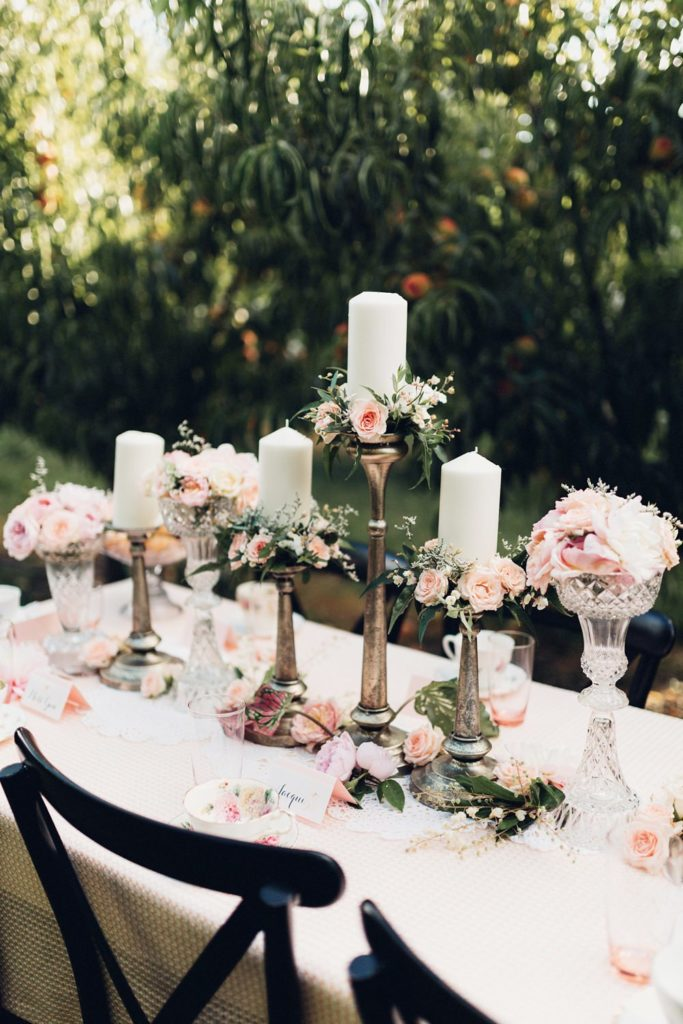 tall gold candle holders with pink flowers and white candles
