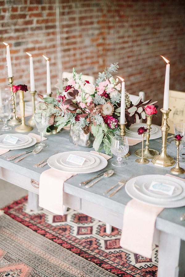 gray table with 6 white plate settings and gold candle holderswith red and pink flowers in the center