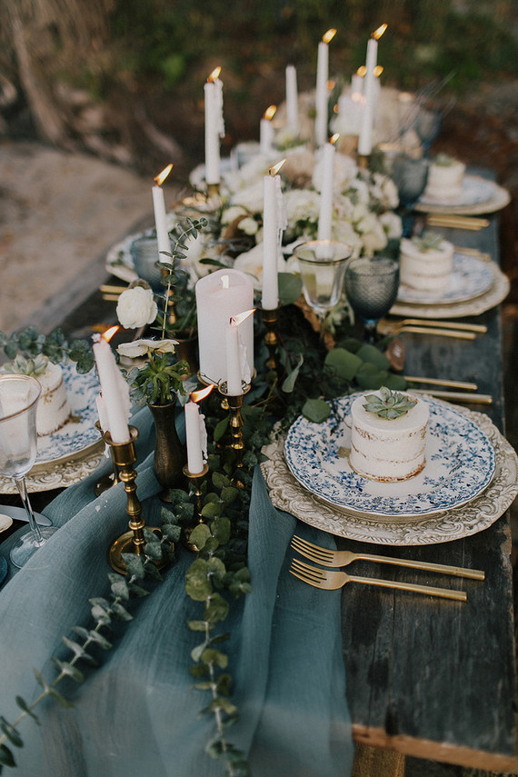 wood table white blue table runner and 6 blue plate with many gold candles in the middle