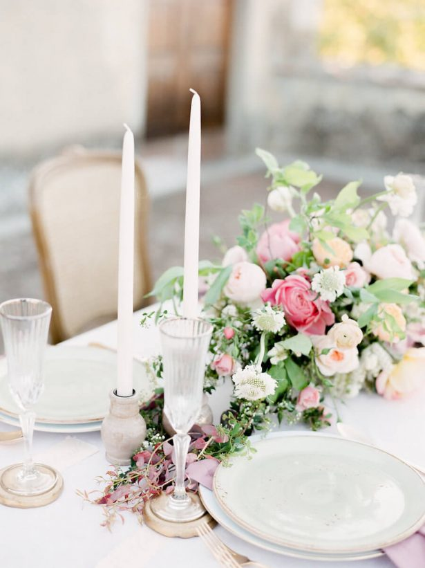 pink and green flower centerpeice with tall white candles and white plates with gold edge