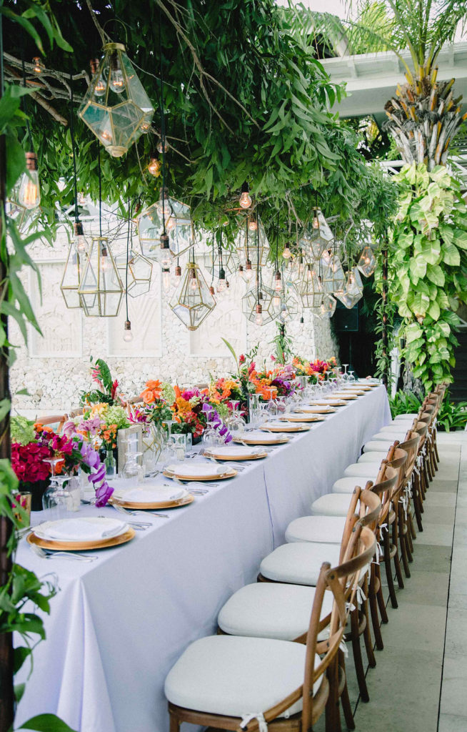 long white table with gold chargers and bright orange red purple flower centerpieces with gold light hanging above