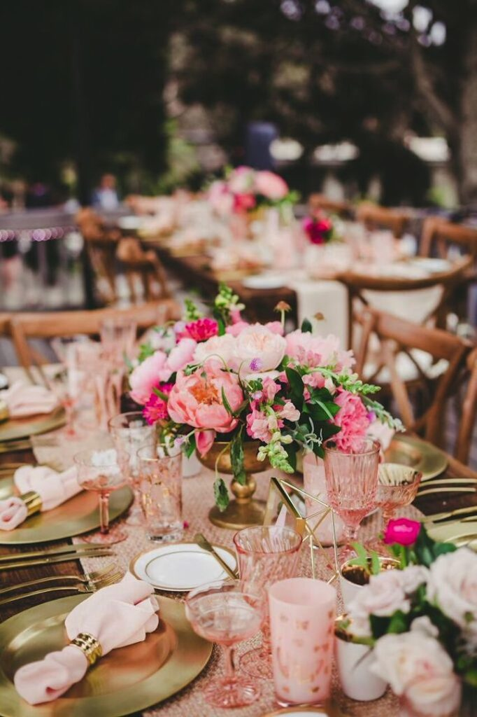 pink cups and pink flowers and gold chargers on wedding table
