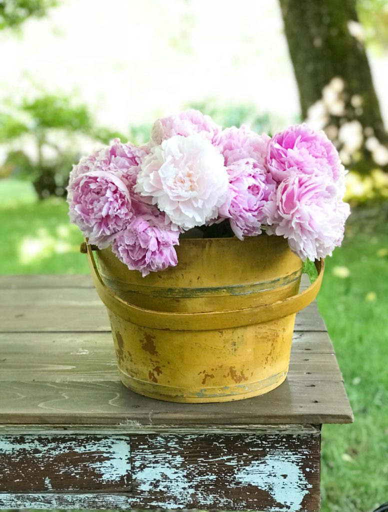 Yellow chippy wood bucket with pink flowers in it