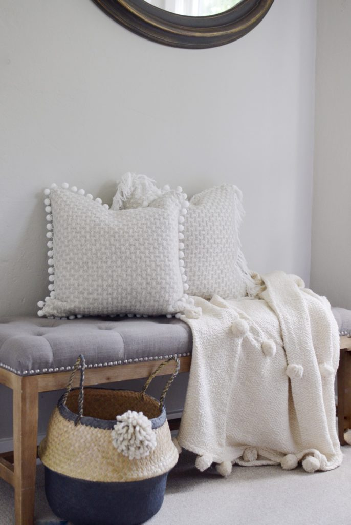 grey tufted bench with 2 pom pom pilows and a cream pom pom blanket with basket on the ground
