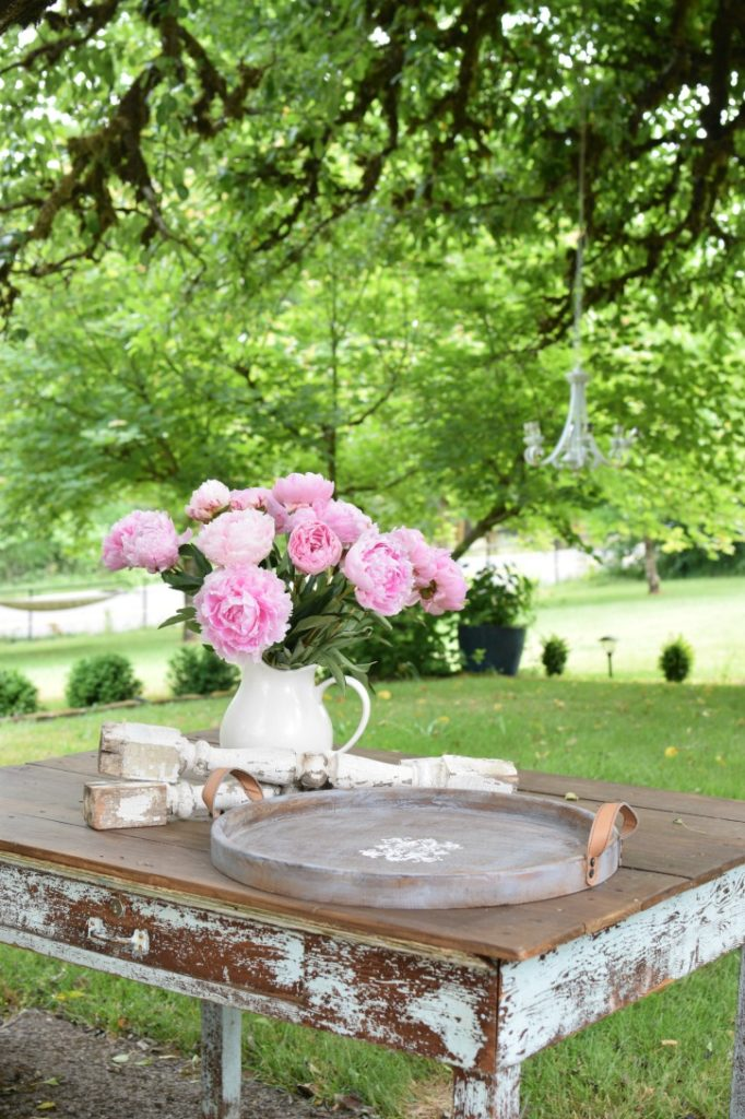 wood table with wood round tray and bouquet of flowers