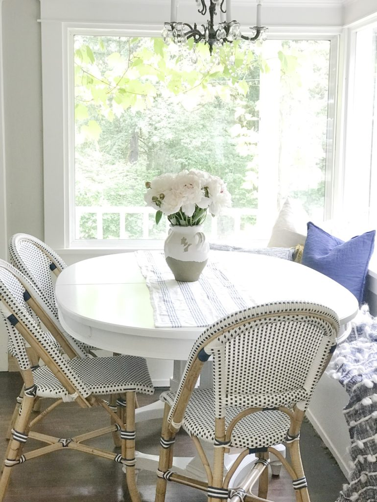 How to Get a Simple Yet Beautiful Farmhouse Style/Home Tour white dining table with 3 blue and white chairs and bench with vase and bouquet of pink flowers