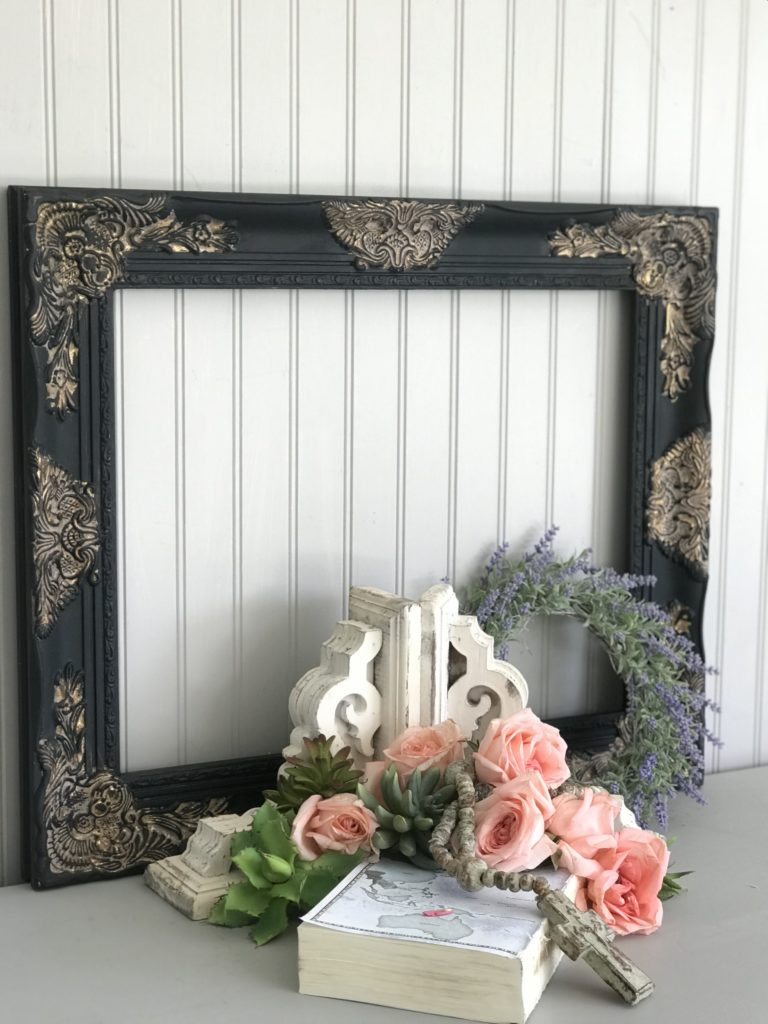 black and gold frame with roses in front