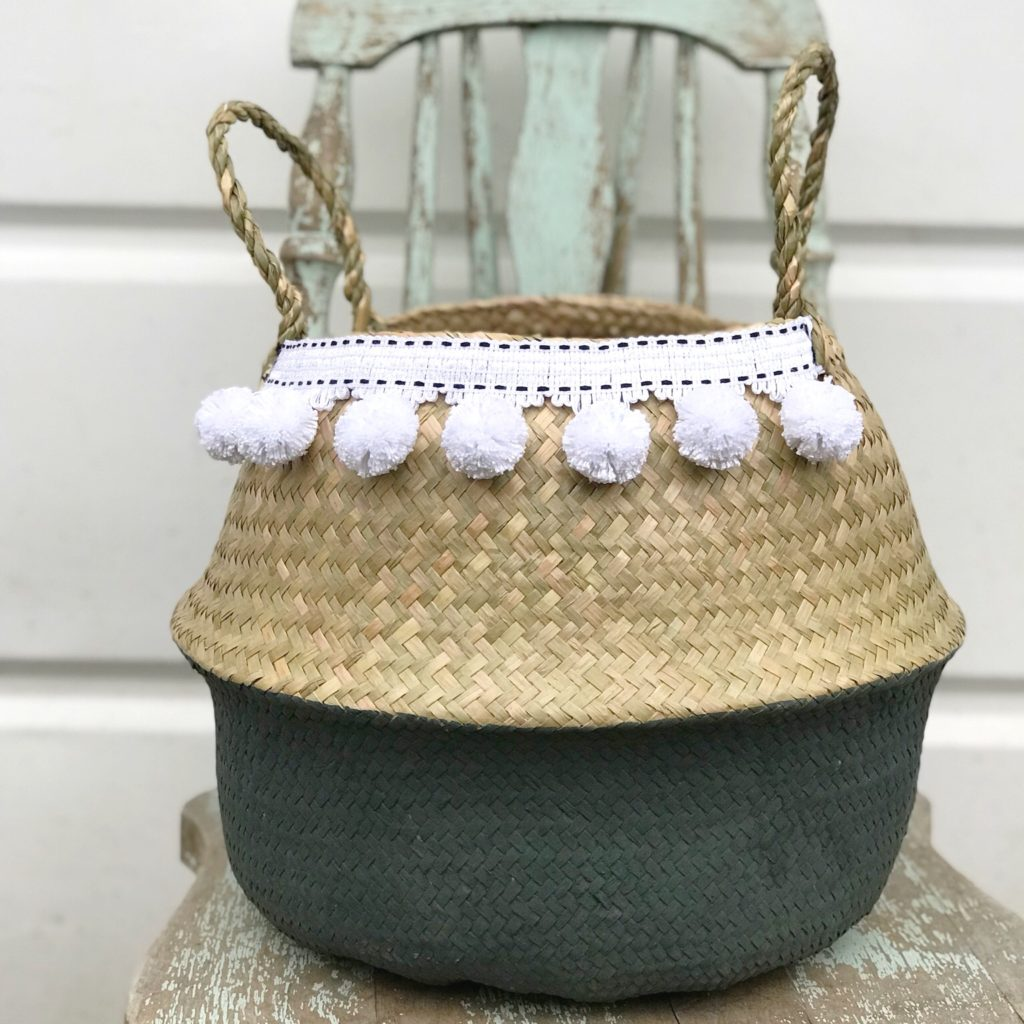 gray woven baskey with white pom poms