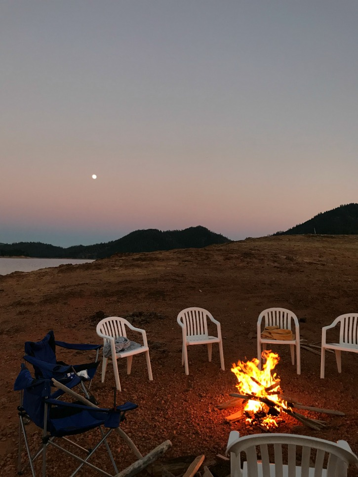 chairs around campfire on shore