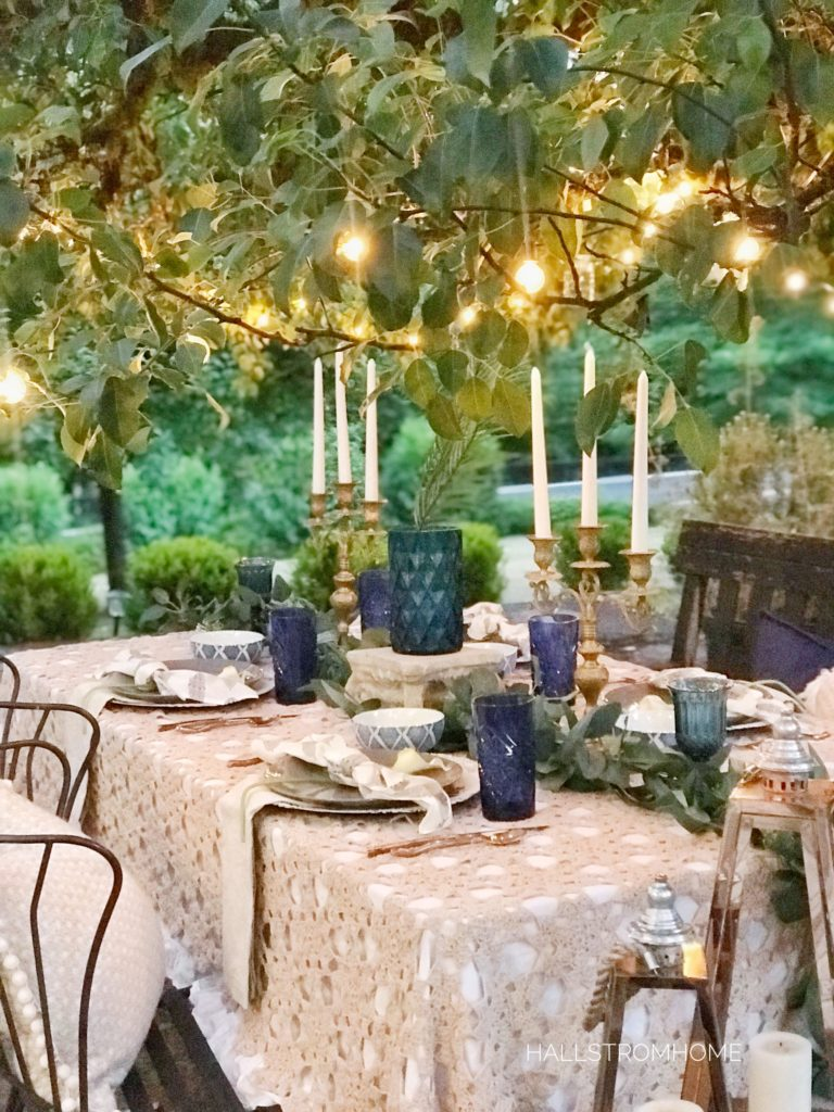 lace table cloth outside with blue cups and vase with gold candelabras and lights above on tree