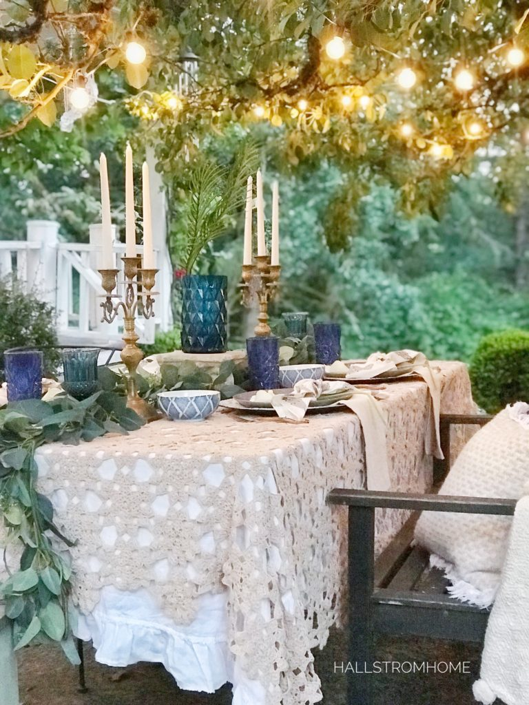 How to Get a Simple Yet Beautiful Farmhouse Style/Home Tour lace table cloth outside with blue cups and vase with gold candelabras and lights above on tree