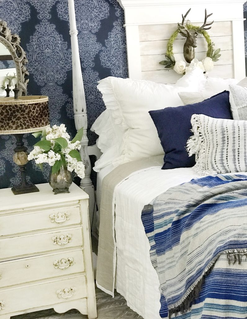 white bedding with blue blanket and 2 blue pillows