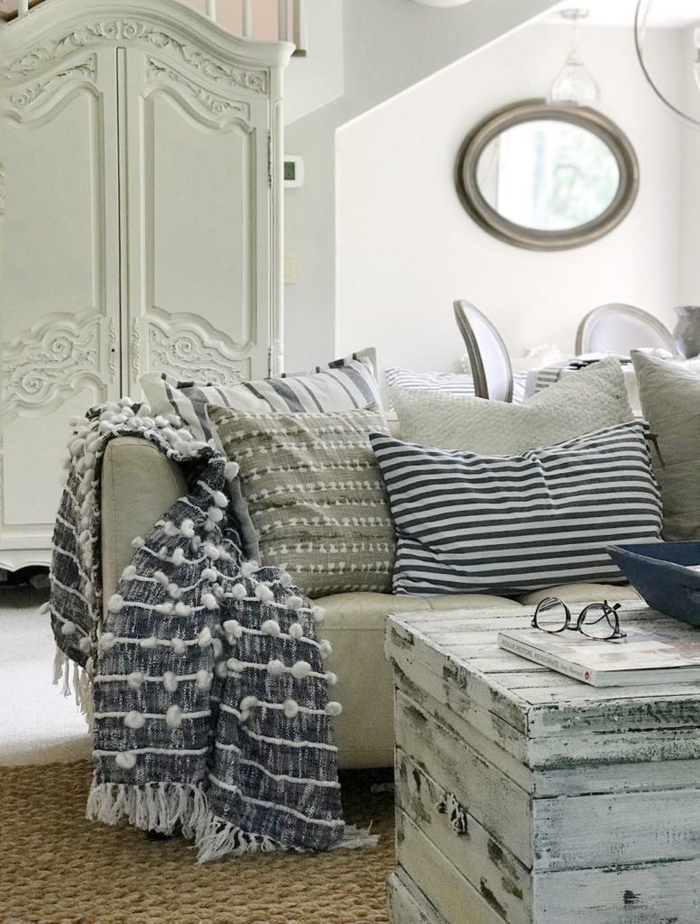white chippy trunk with couch and blue blanket with 5 blue and white and natural pillows