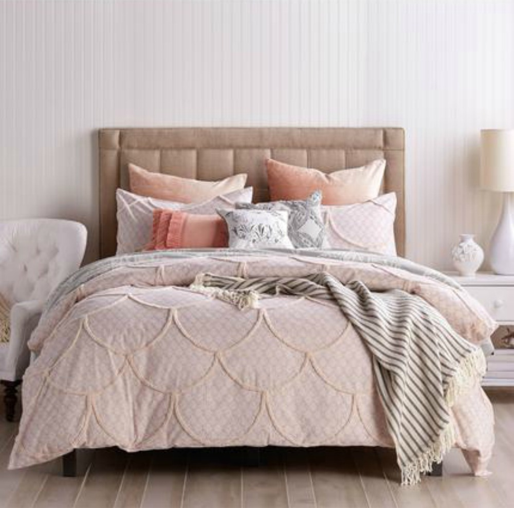 scalloped pink bedding with draped striped blanket tufted headboard with 7 pillows