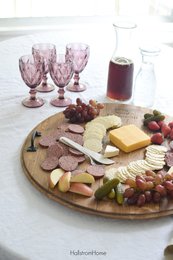 How to Make a Wine Barrel Cheese Board the Easy Way with cheese crackers pickles apples and four glasses