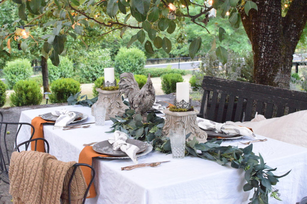 white linen table cloth qith greenery in middle and 2 candle pedestals with rooster in centerpiece