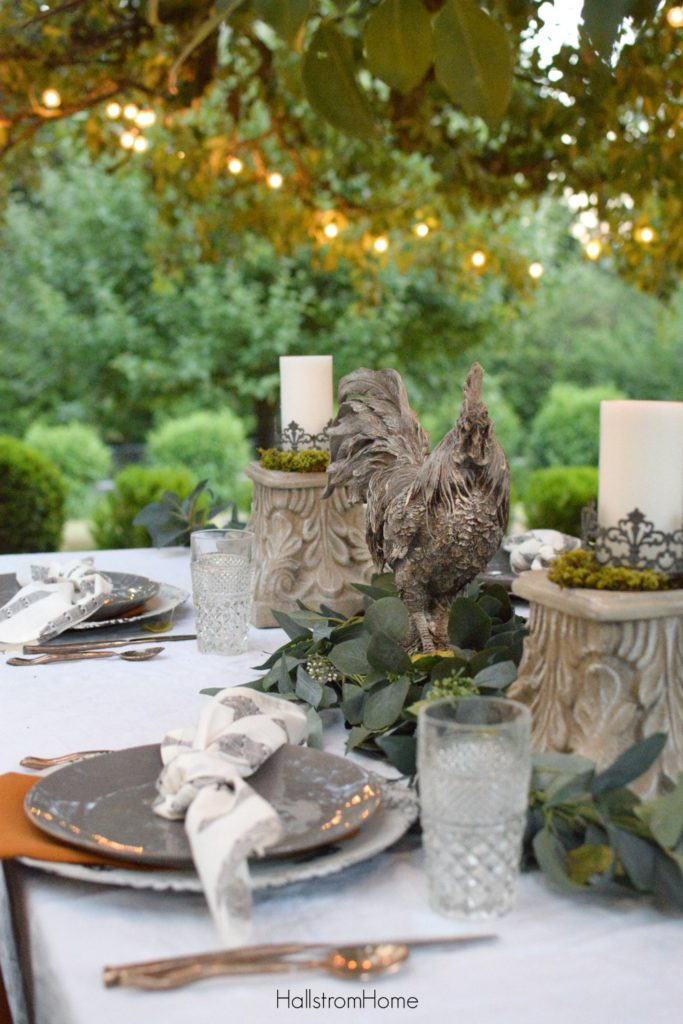 fall table with rooster centerpiece and 2 candle pedestals