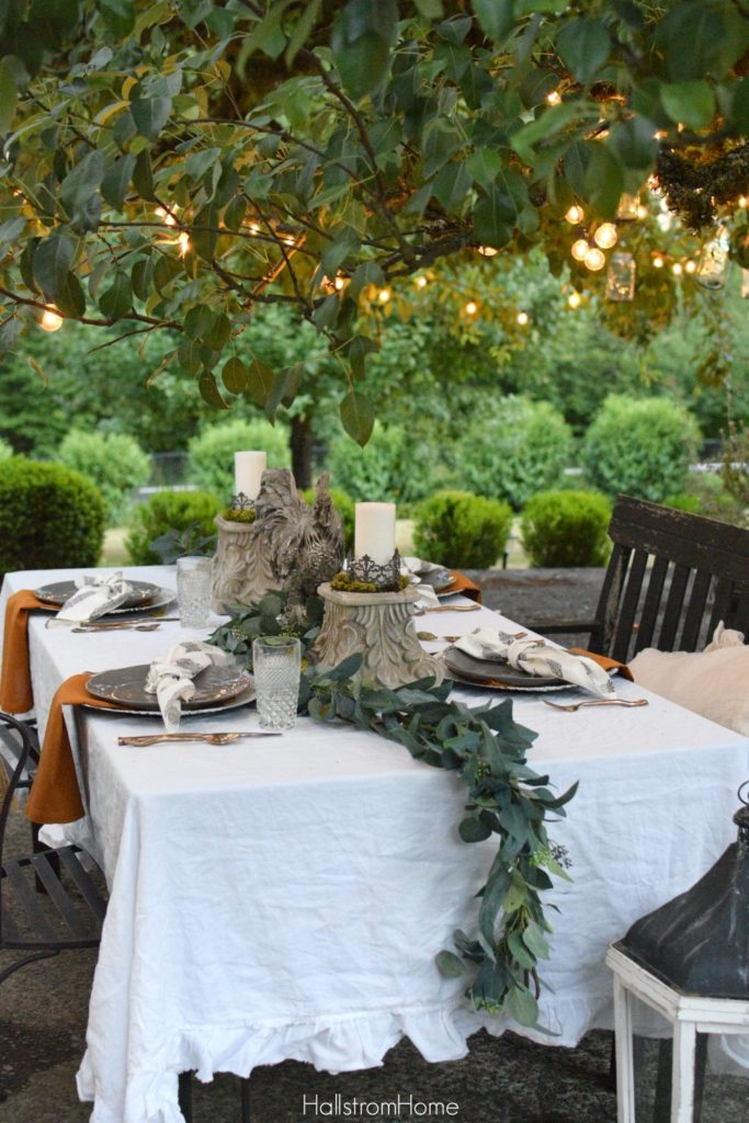 Celebrate Autumn with the Most Perfect Tablescape with orange sweater on chair and rooster and 2 candle pedestals as centerpiece with greenery down middle