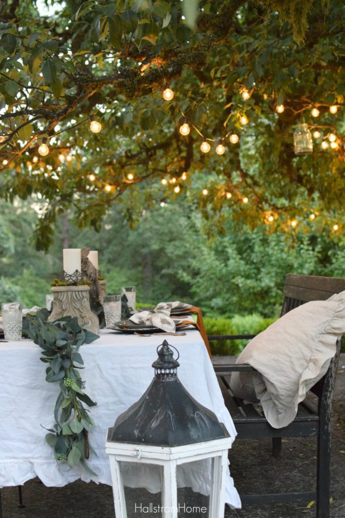 fall table with roostr centerpiece and greenery down middle with bench full of linen shams