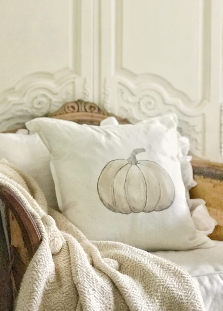 white pumpkin pillow on wooden chair with knit pom pom blanket