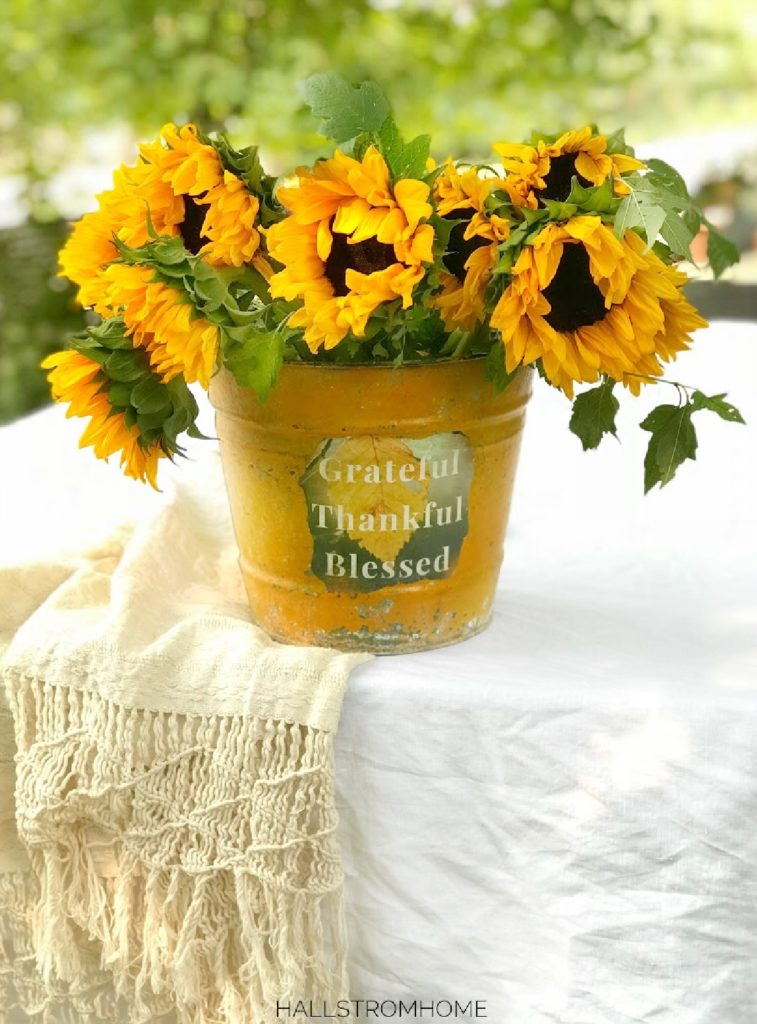 yellow bucket with sunflowers on white linen table cloth