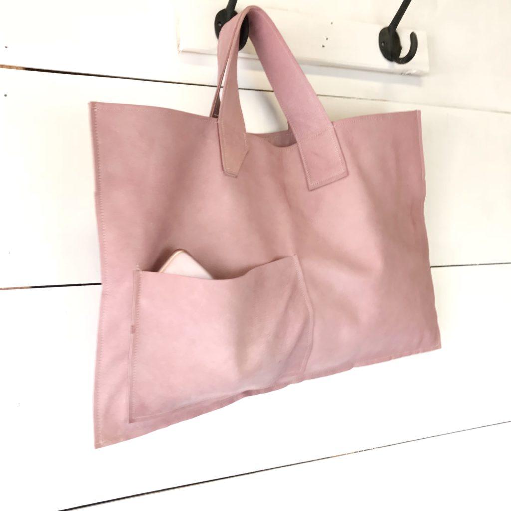pink leather bag hanging on hook