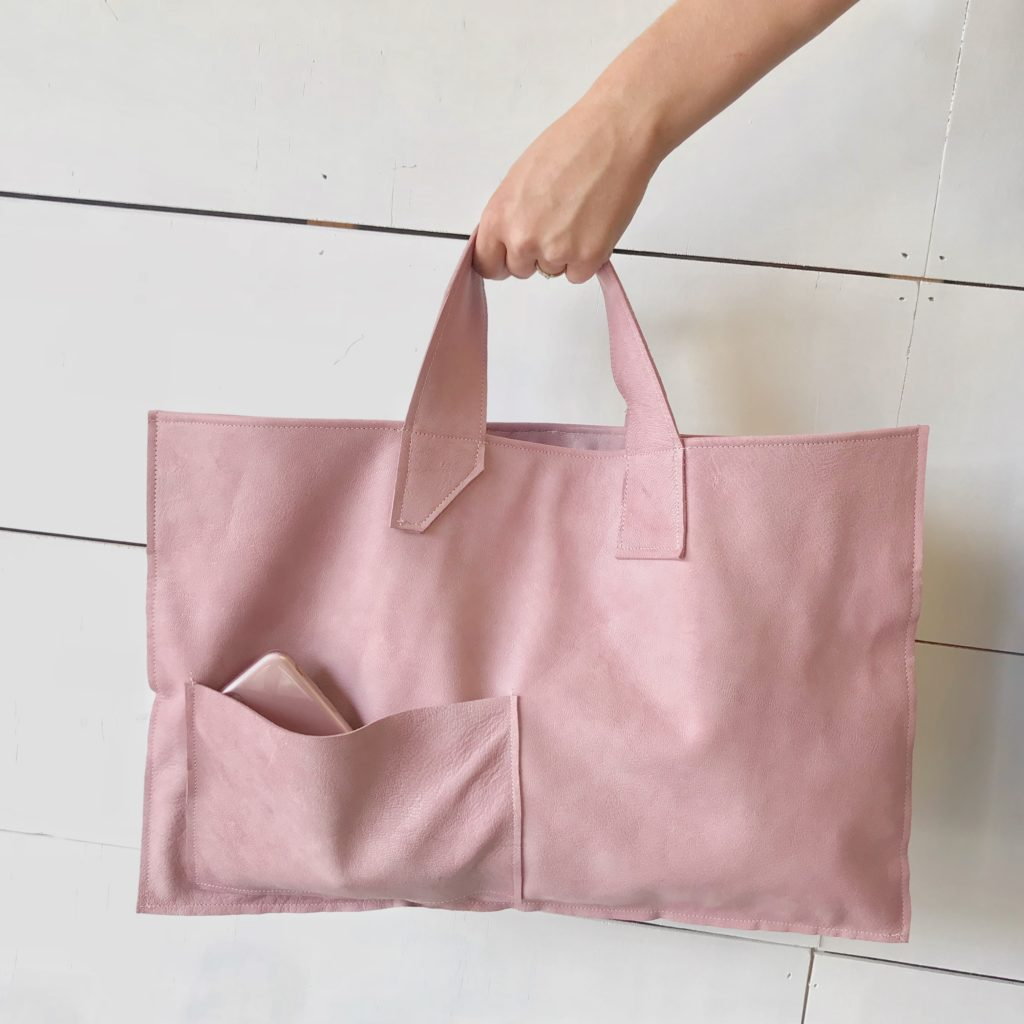 We Have a Fabulous Surprise-Launching a New Product, What Do You Think? hand holding pink leather bag with phone in front pocket
