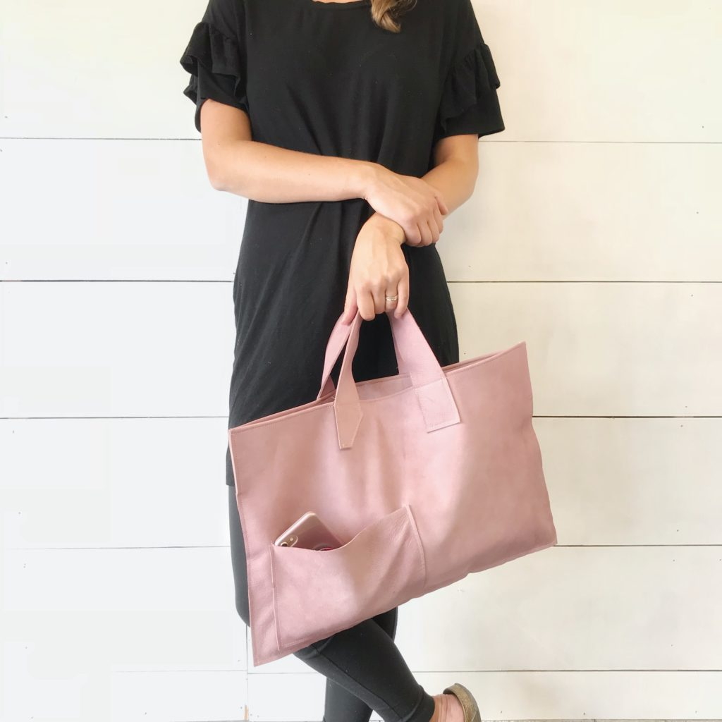 We Have a Fabulous Surprise-Launching a New Product, What Do You Think? in black holding pink leather bag