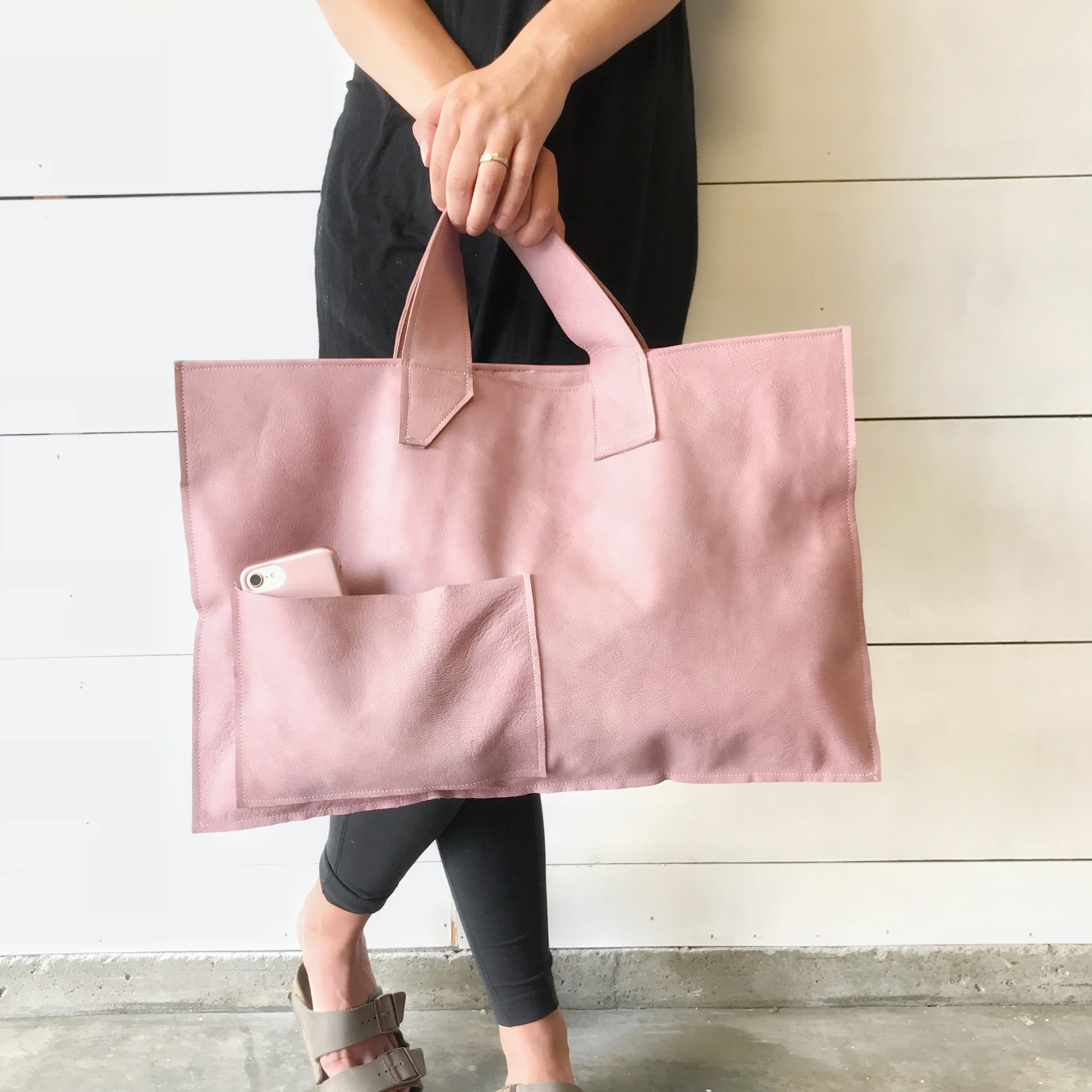 girl in black holding large pink leather bag