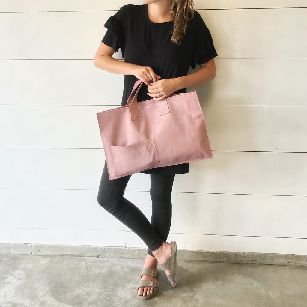 girl in all black holding pink leather bag
