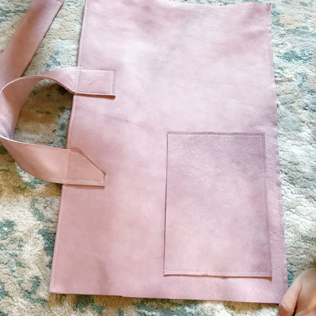 pink leather bag laid out on ground