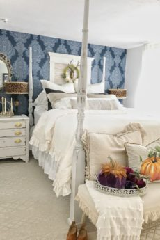 How to Decorate Bedrooms for Easy Fall Decor cream bedding with 8 pillows and velvet pumpkins on bench in front and pumpkin pillow