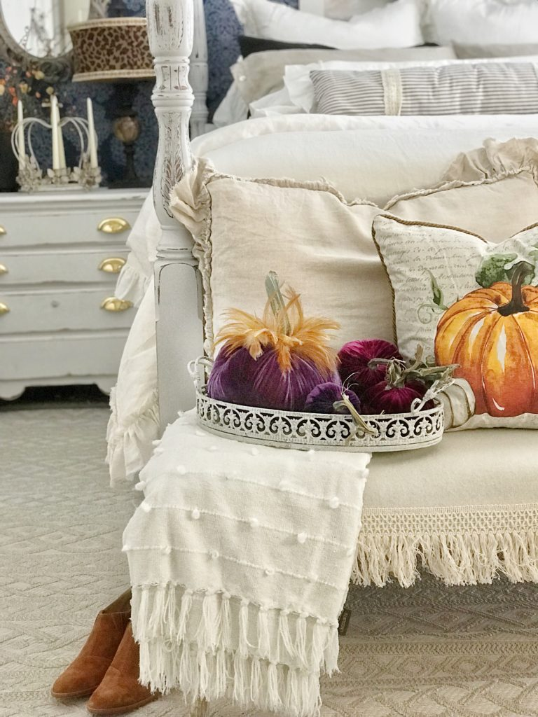 linen ruffle bed with purple velvet pumpkins on bench in front of bed