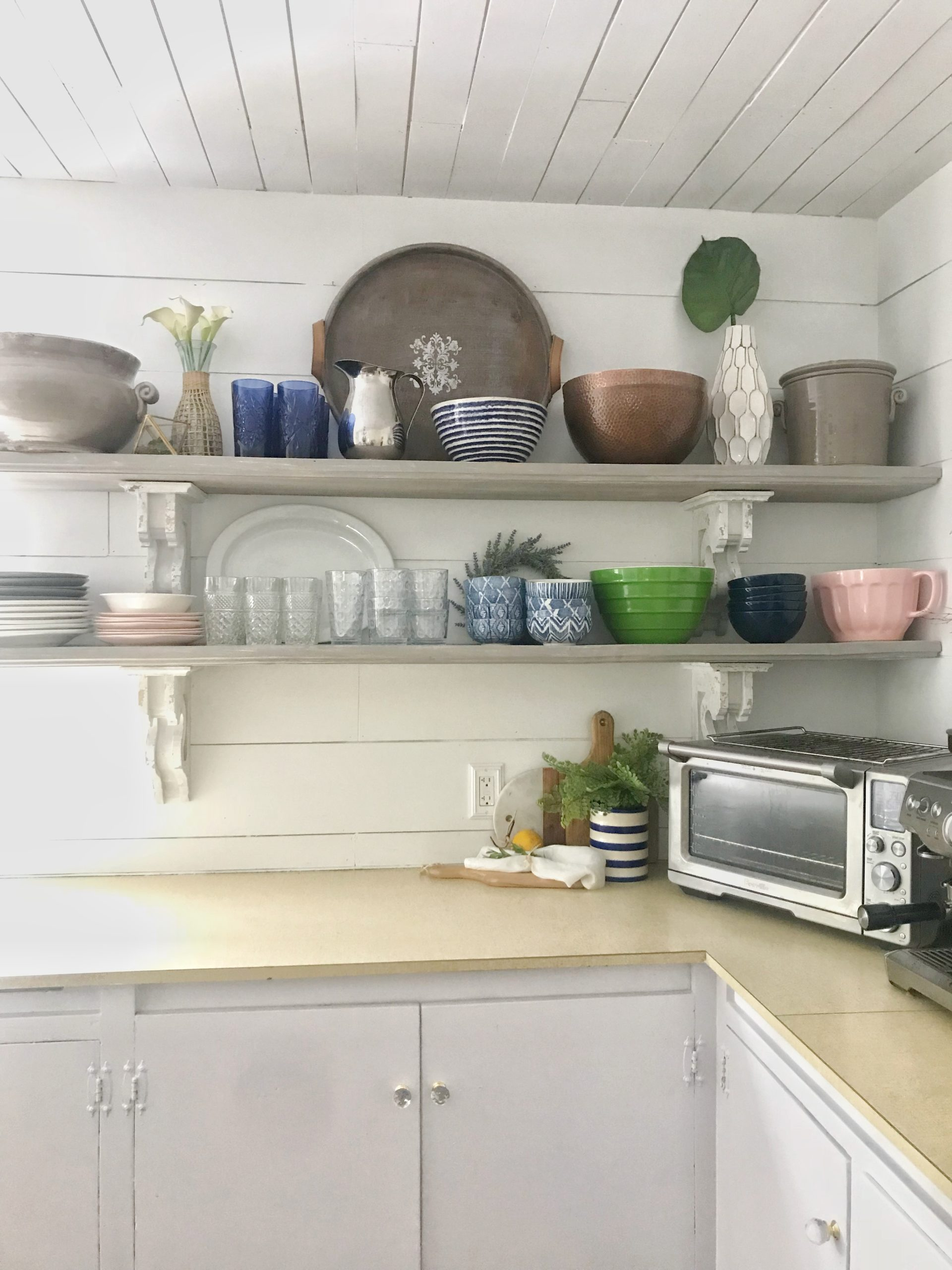 kitchen with 2 openshelves filled with bowlscups and plates