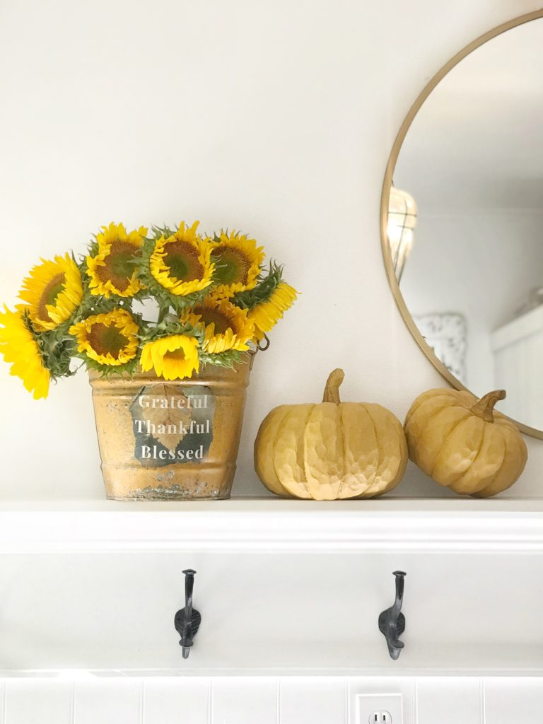 mantel with 2 yellow pumpkins and yellow metal bucket with sunflowers and gold round mirror hanging