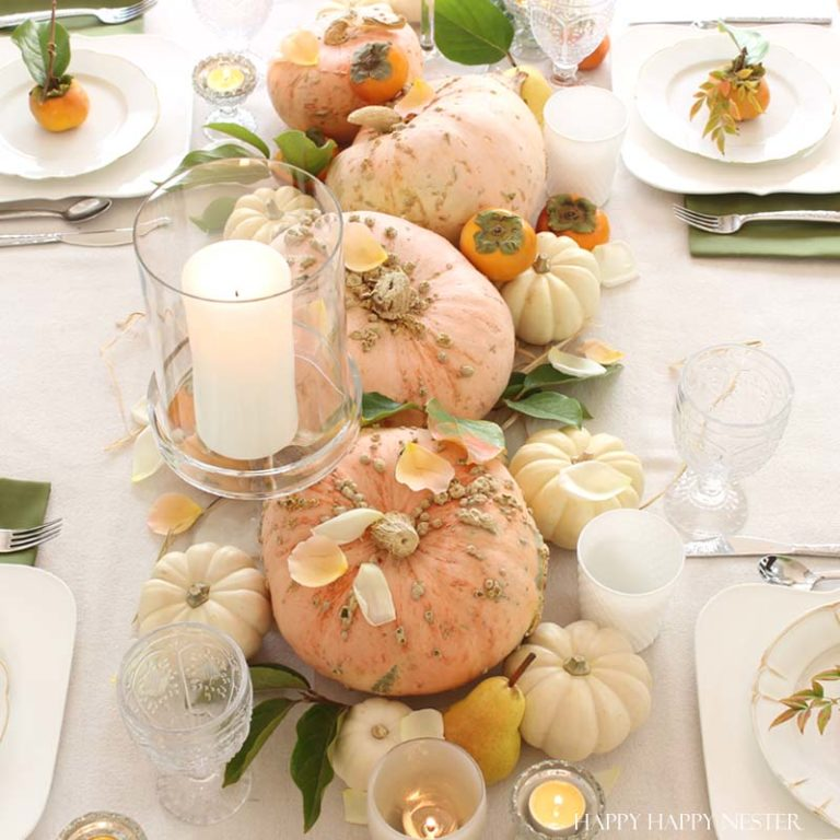 pumpkin on middle of table with glass candle holders and table set