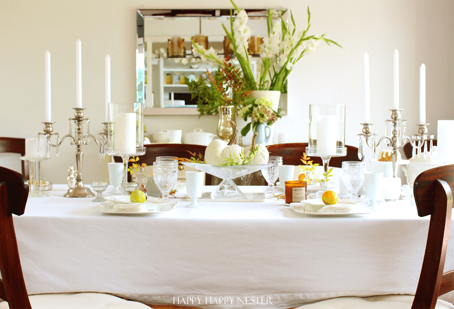 white table cloth with 2 candelabras and table setting with oranges